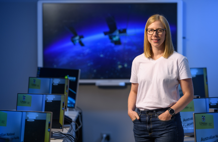 Dr Courtney Bright stands inside a computer lab, smiling with her hands casually in her pockets. Behind her is a large screen featuring a vision of the M2 satellite.